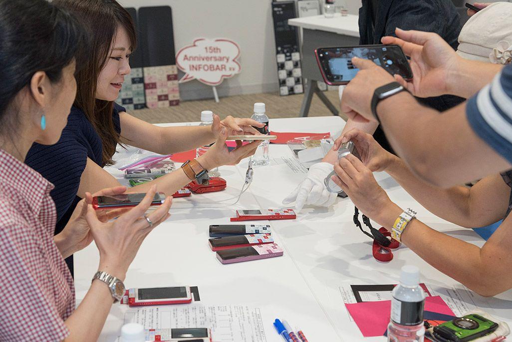 INFOBARファンミーティング新宿で披露されたINFOBAR xvのデザインモックを撮影する参加者たち