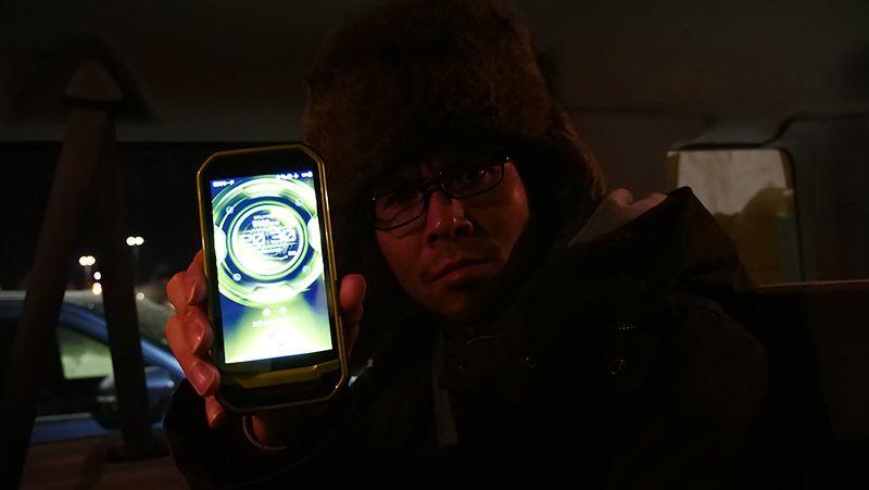 クルマの中でTORQUE G03をカメラに見せる地主