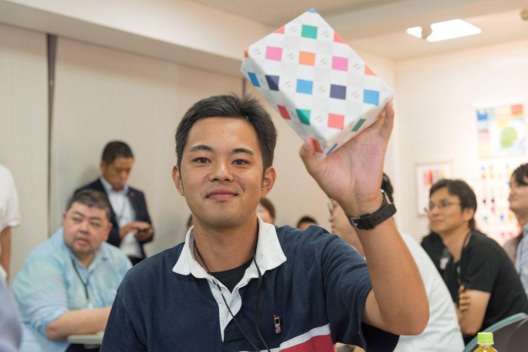クイズ大会の優勝賞品を掲げる男性