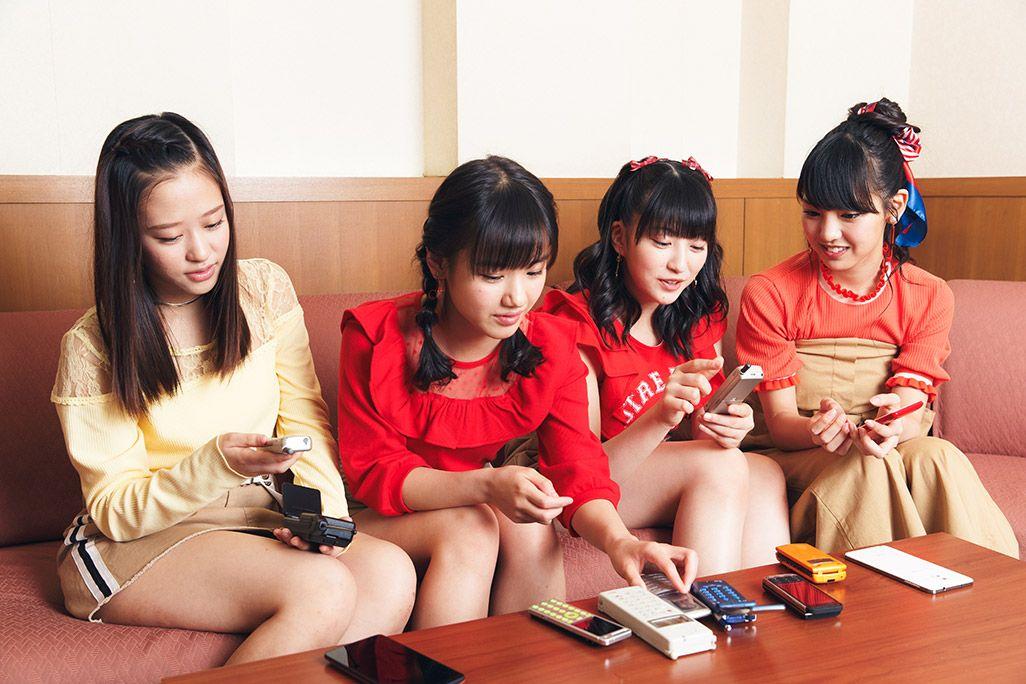 古い携帯電話に触れながら未来に想いを馳せる飯窪春菜、羽賀朱音、横山玲奈、小田さくら
