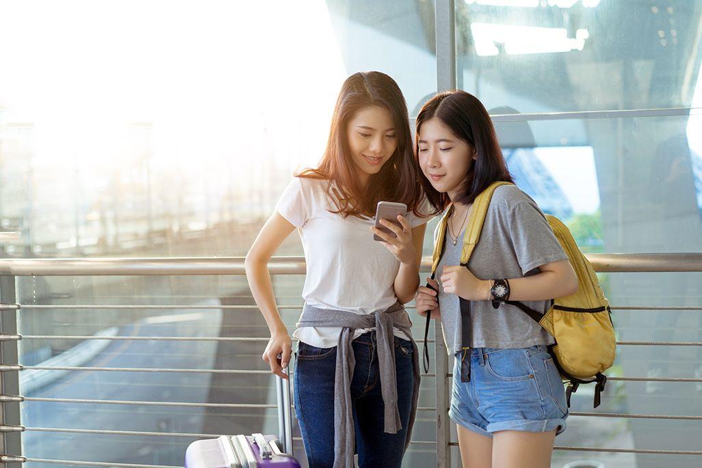 空港でスマホを見る女性2人