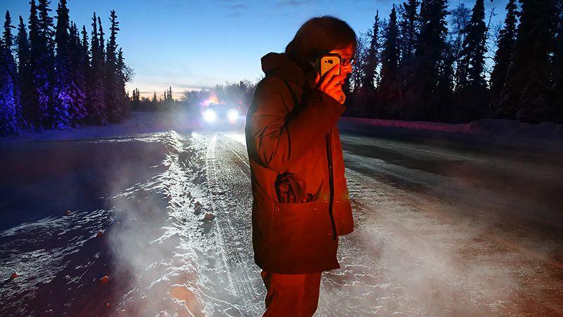 アラスカの道路で電話する地主