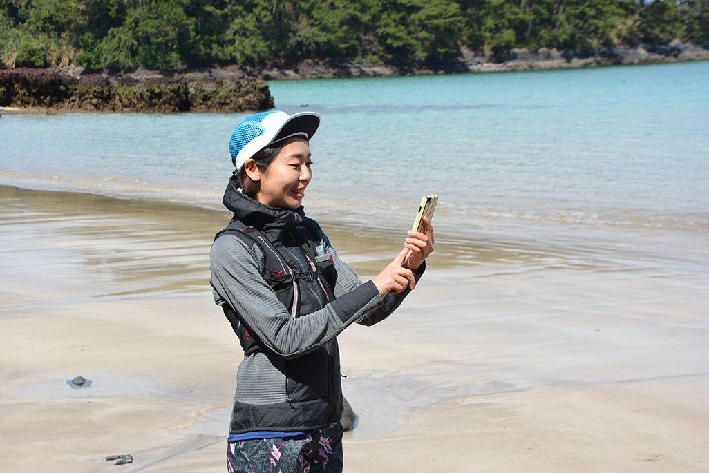 小値賀島の柿の浜海水浴場でスマホを操作する浦谷美帆さん