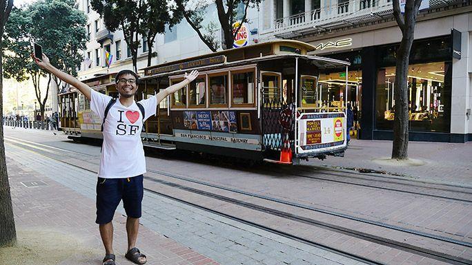 新しく買ったTシャツを着て路面電車の前でポーズをする地主