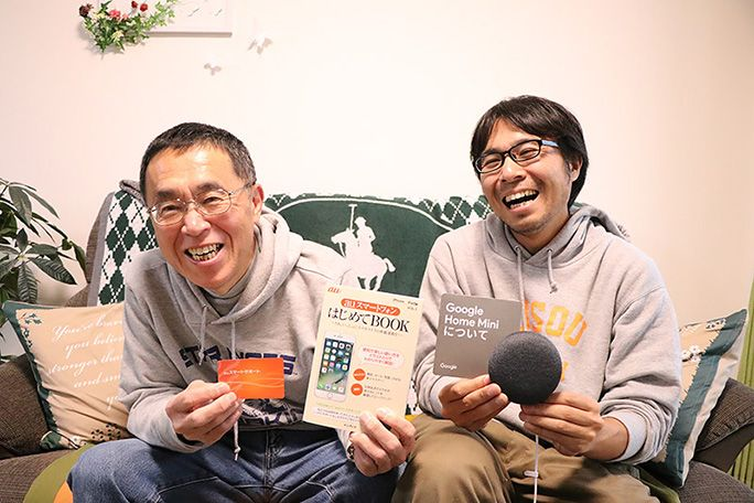 Google Home Mini と「はじめてBOOK」、会員カードを手に笑顔の地主親子