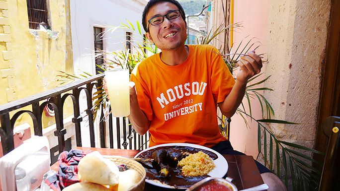 「モレ」を食べて笑顔を浮かべる地主