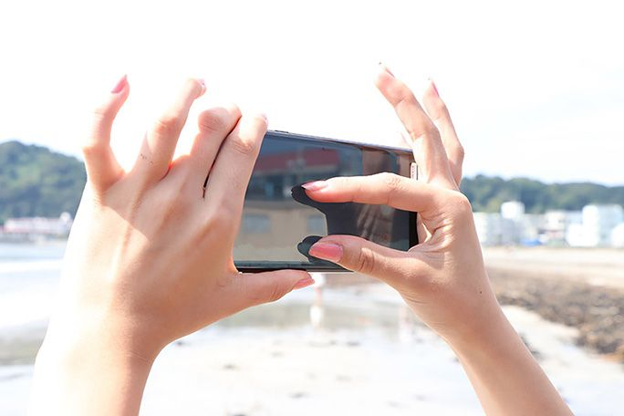 インスタ映えの風景を拡大する女性の手