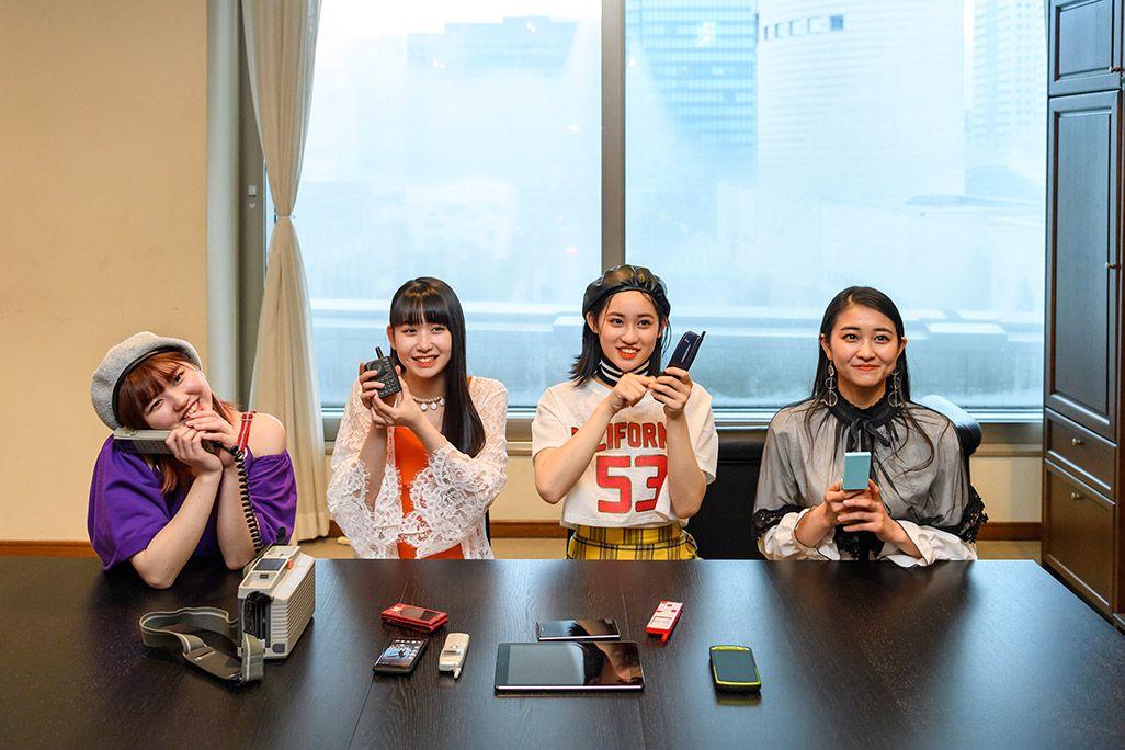 古い携帯電話を手に微笑むアンジュルムの和田彩花、佐々木莉佳子、笠原桃奈、竹内朱莉