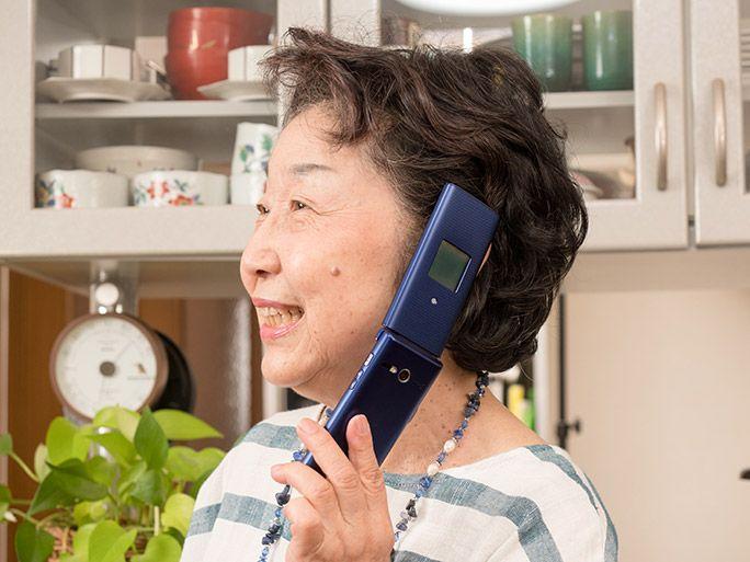 高齢者向けのケータイ「かんたんケータイ KYF38」で通話する女性