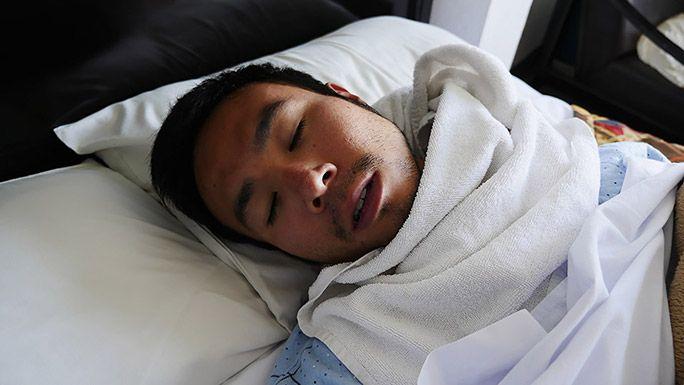 ホテルのベッドに横たわる地主