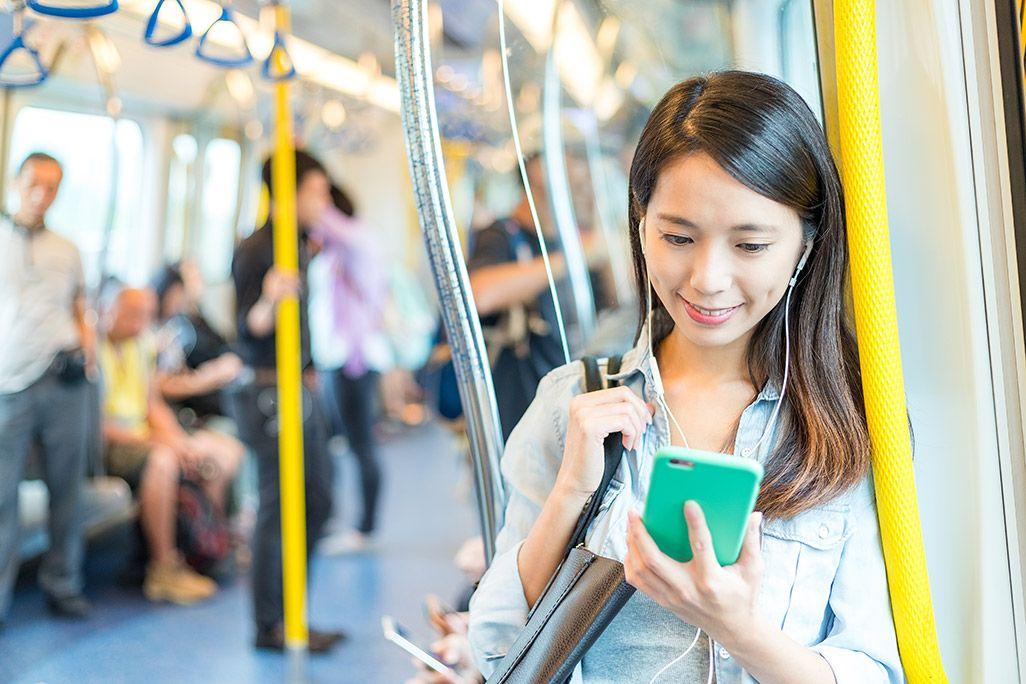 電車でスマホを使う女性