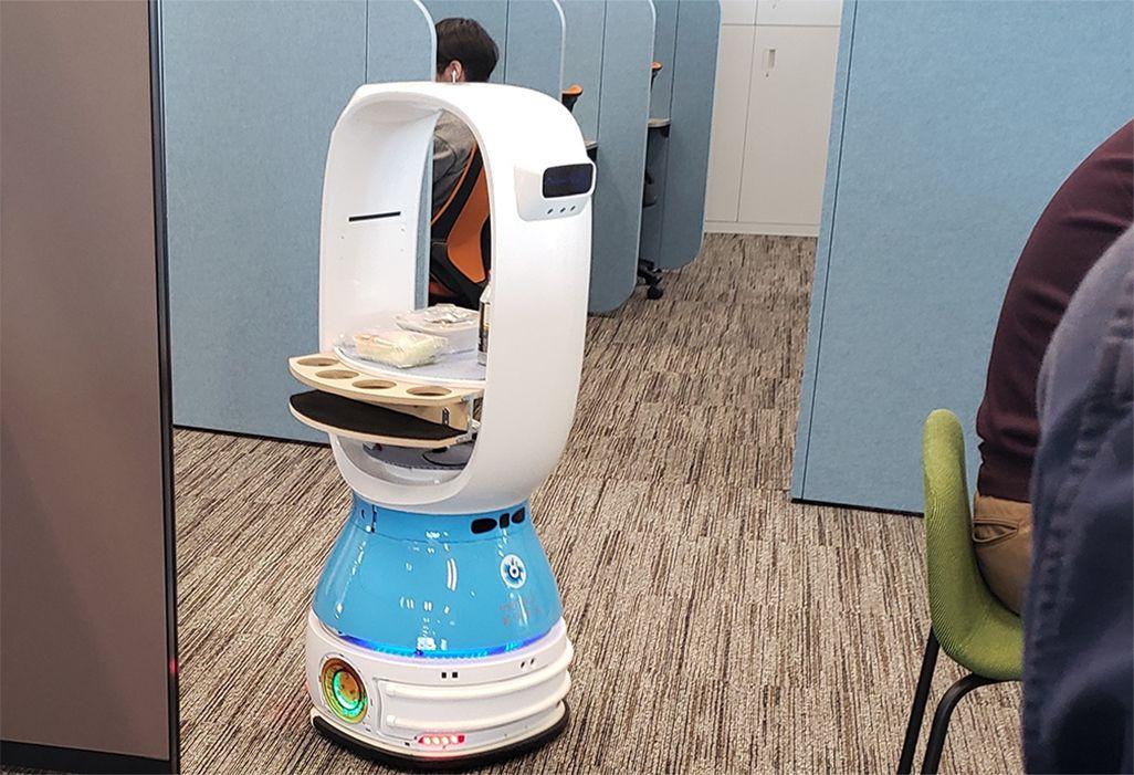 ロボットがオフィス内でデスクに飲み物を運ぶ