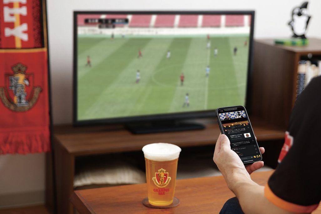 サッカーの試合を見ながら「名古屋グランパス公式アプリ」で自宅から応援する様子