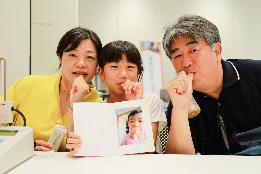 おもいでケータイ再起動でプリントした写真を手にポーズをとるご家族