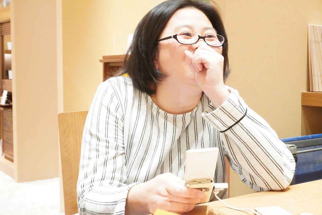ケータイ片手に笑う女性