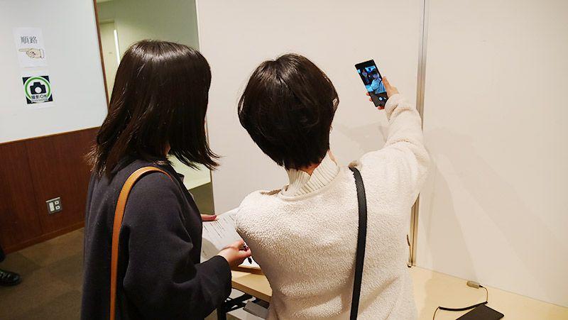 スマートフォンで自撮りを試す若い女性2名の後ろ姿