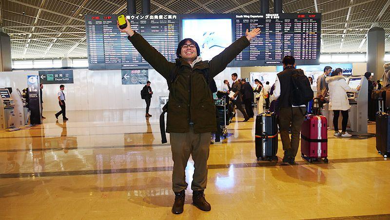 空港の出発ロビーで TORQUE G03を持ち両手を広げる地主