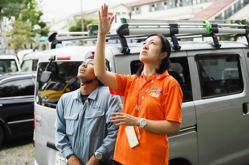 施工会社のスタッフに上諏訪駅前に設置した車載型基地局のアンテナの調整内容を指示する杉村