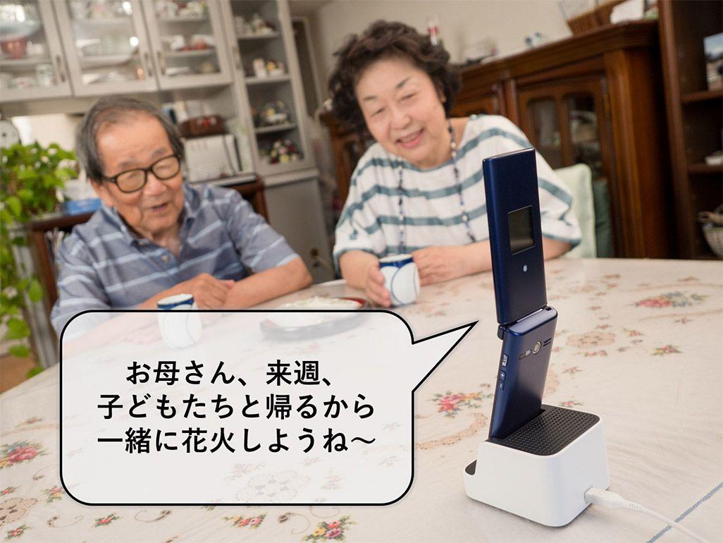 卓上ホルダのスピーカーを使い、高齢者向けのケータイ「かんたんケータイ KYF38」で娘と会話する夫婦
