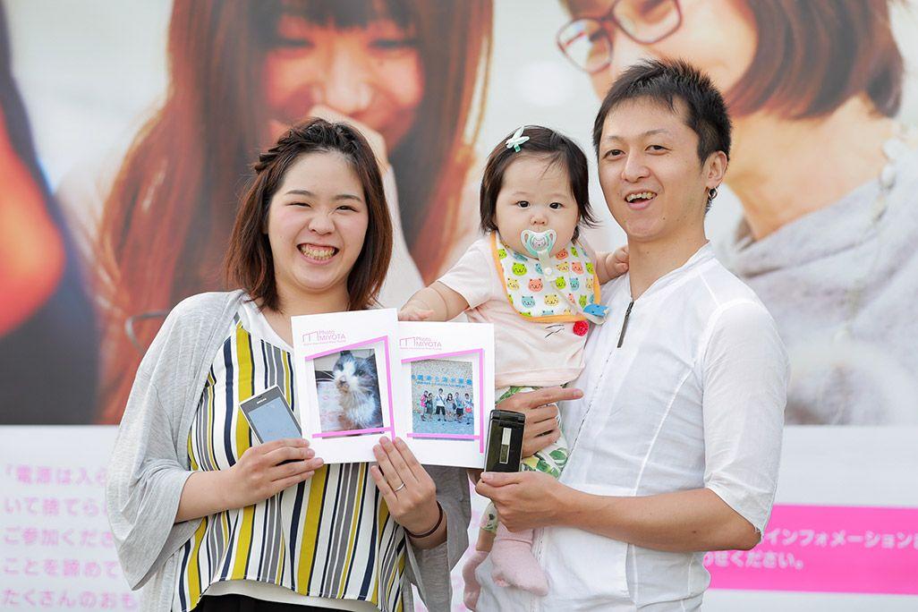 「おもいでケータイ再起動」でプリントした写真を手に微笑む夫婦と子ども