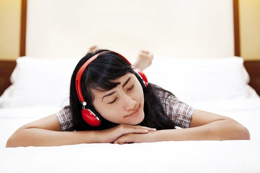 ベッドで音楽を聴いている人