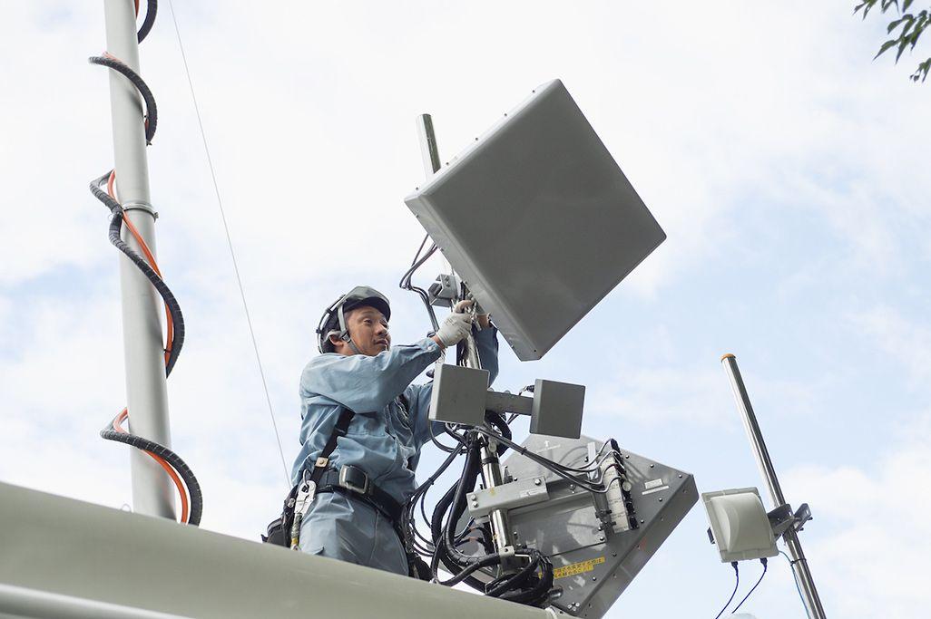 上諏訪駅前に設置した車載型基地局のアンテナの角度を調整する施工会社のスタッフ