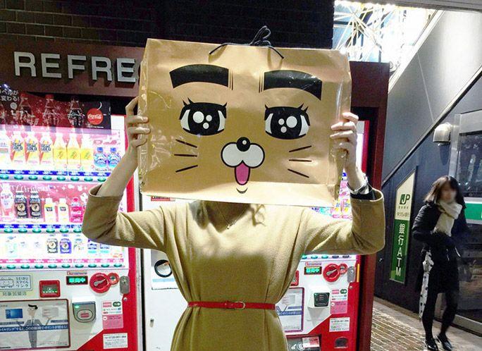 ネコの顔が描いてある紙袋を自分の顔にあてる筆者