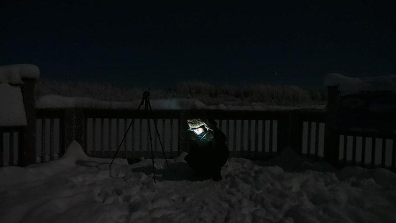 雪原の中で座りながらTORQUE G03を見る地主