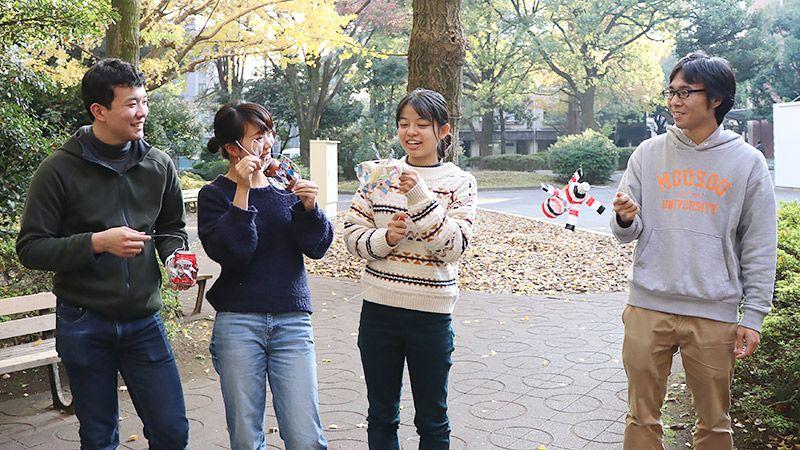 大学生と手作りの風車をもちながら談笑するライターの地主恵亮