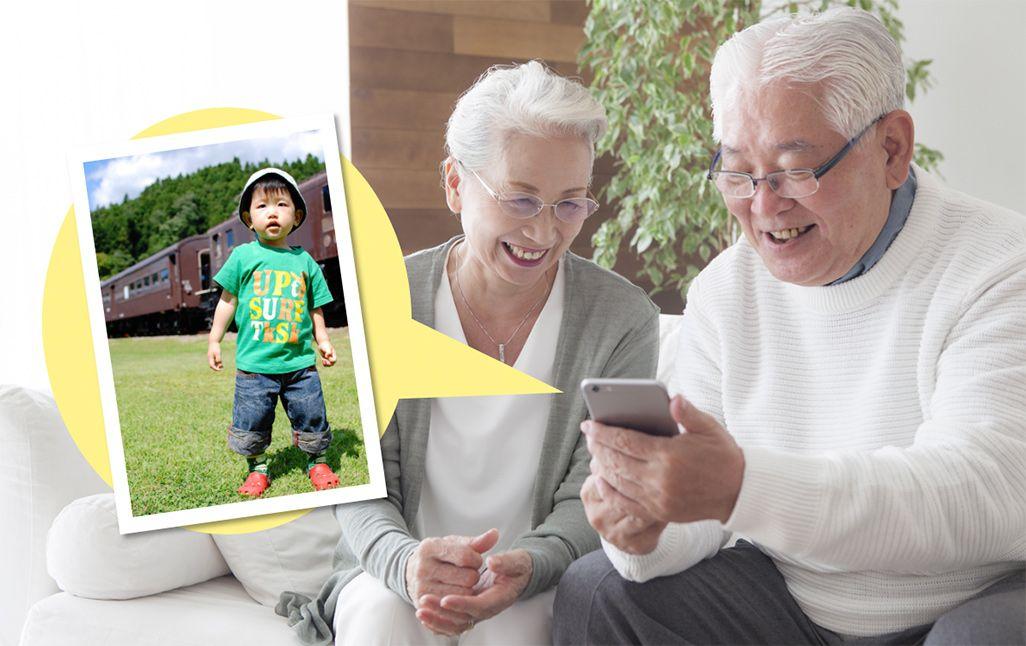 スマホで孫の写真を見る祖父母