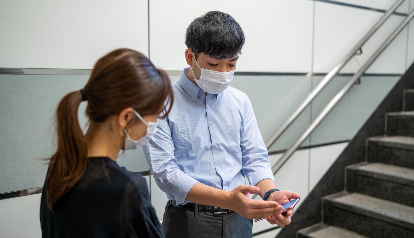 新宿駅の地下出口でau5Gの通信エリアを調査をする人