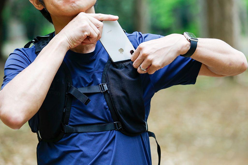 バックパックを背負ってiPhoneを取り出す男性