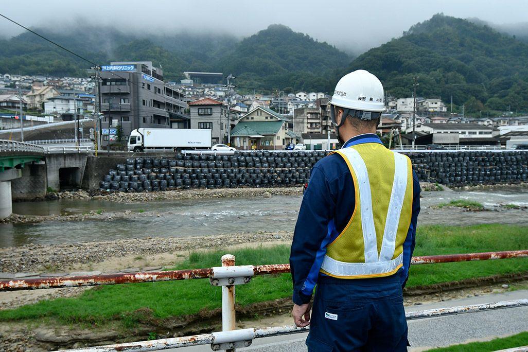 川を眺める作業着姿の男性