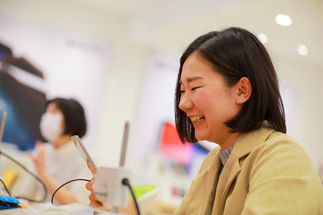 au 昔、使っていたケータイを見つめて笑う女性