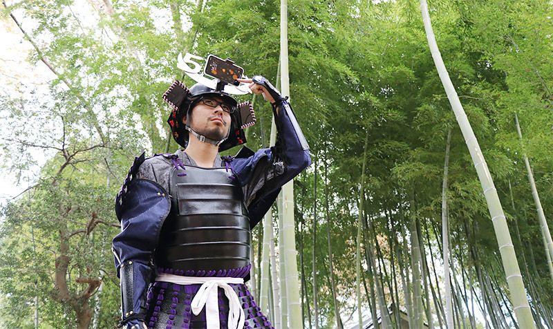 竹藪で甲冑姿で頭上のスマホを触るライターの地主恵亮