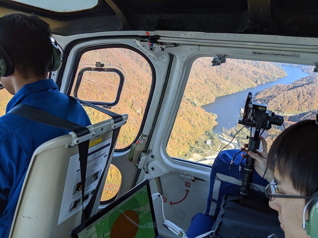 上空からヘリコプターで地上に向けて電波を発信