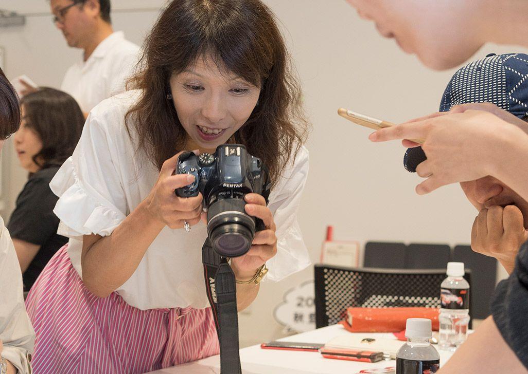 INFOBARファンミーティング新宿で披露されたINFOBAR xvのデザインモックを撮影する参加者