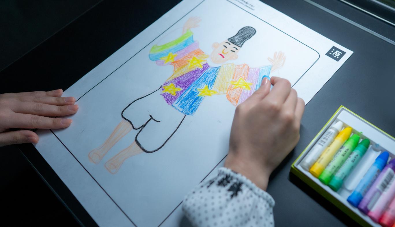 KDDIのコンセプトショップ GINZA 456 とチームラボとのコラボによる体験型イベントWalk, Walk, Walk Home で紙にぬり絵する女性