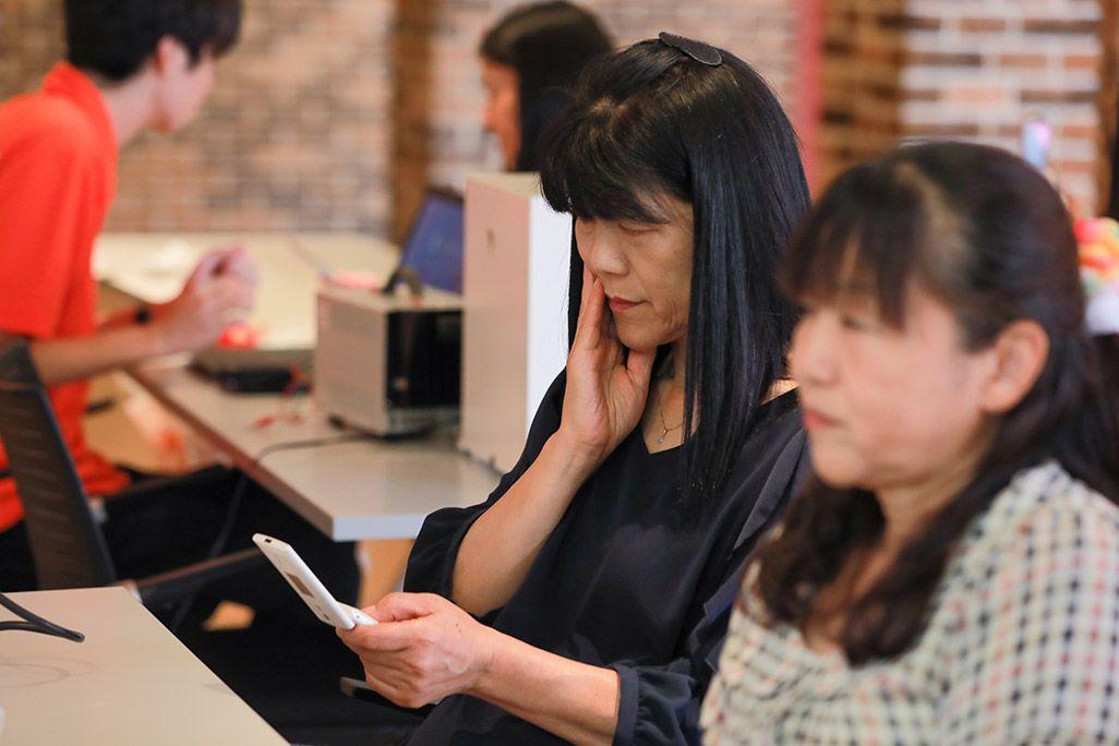 「おもいでケータイ再起動」で復活したケータイのディスプレイを見る女性