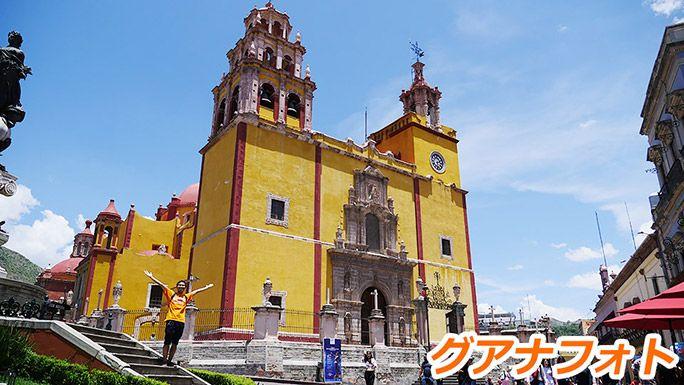 グアナフォトのカラフルな建物の前でポーズをする地主