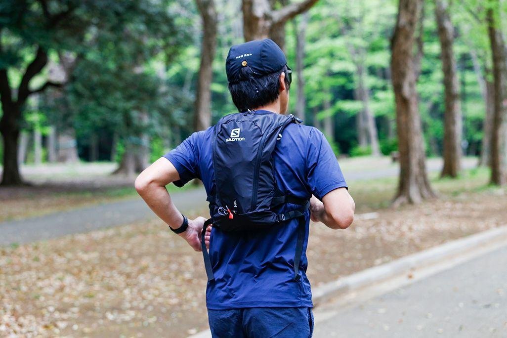 バックパックを背負って公園を走る男性