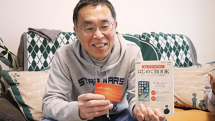 auスマートサポートのカードと加入特典の「はじめてBOOK」を持つ父