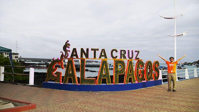 ガラパゴスのモニュメントの前で両手を広げて写真に写る地主