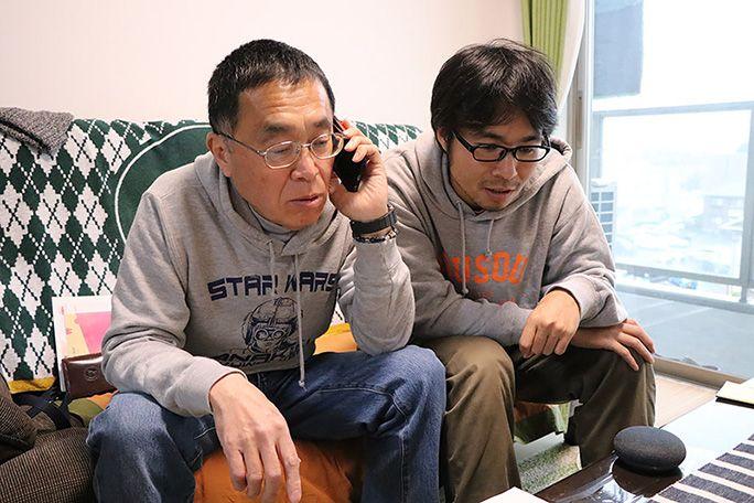 auスマートサポートに電話する父と横に寄り添う地主