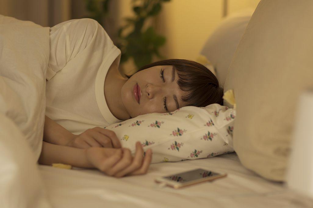 スマホを枕元に置いて眠る女性