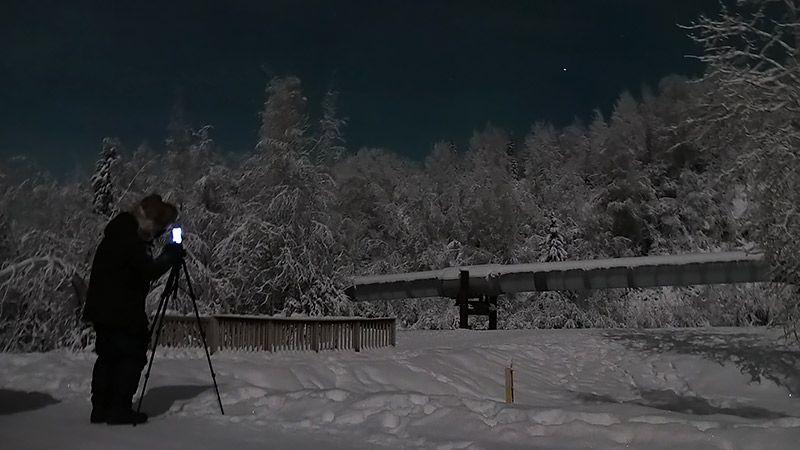 アラスカの雪原の中でTORQUE G03を構えるライターの地主