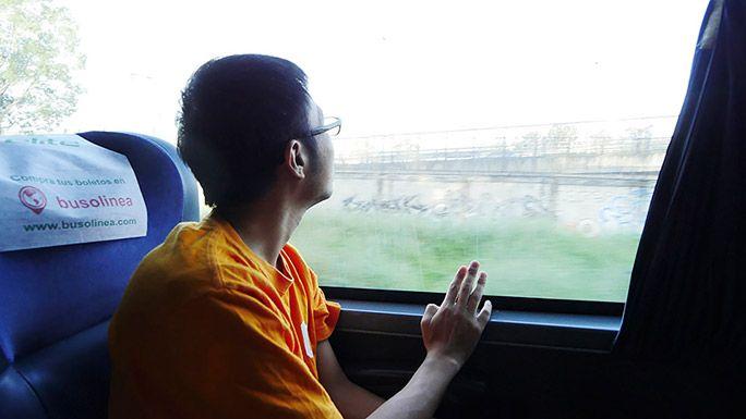 バスに乗車し、窓の外を眺める地主