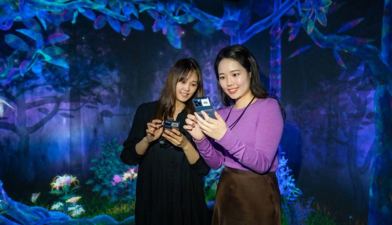KDDIのコンセプトショップ GINZA 456 とチームラボとのコラボによる体験型イベント「捕まえて集める境界のない群蝶」に参加した女性の写真
