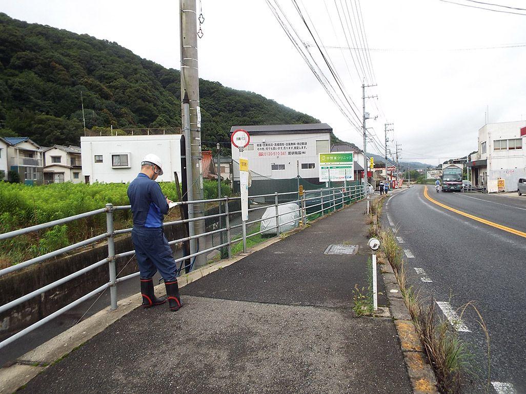 国道線沿いで光ケーブルの仮設ルートを検証する作業着姿の男性