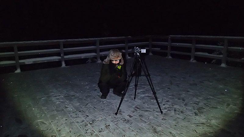 三脚を立てて雪原でオーロラをしゃがみながら待つ地主